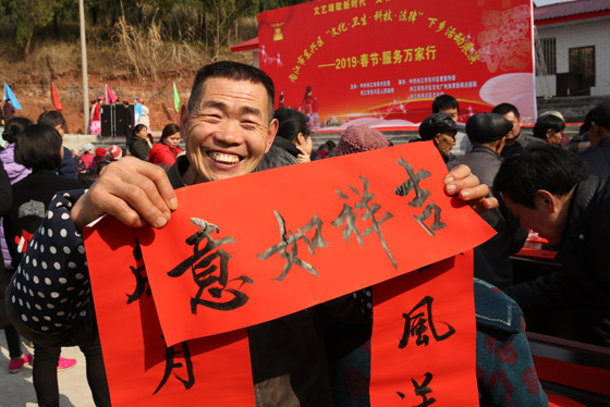 内江春节到来时政府开展送文化下乡活动,一村民拿到新写就的春联喜笑颜开 兰自涛 摄.JPG